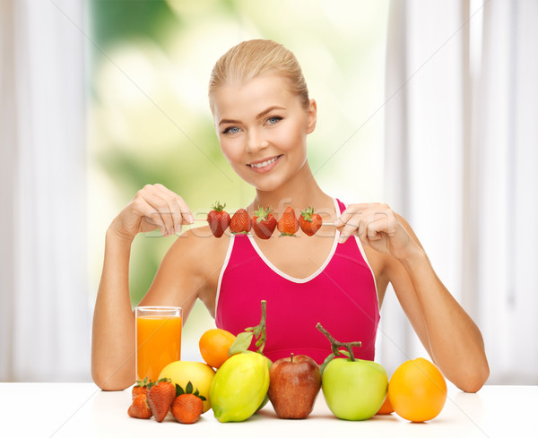 Kadın organik gıda yeme çilek genç kadın meyve Stok fotoğraf © dolgachov