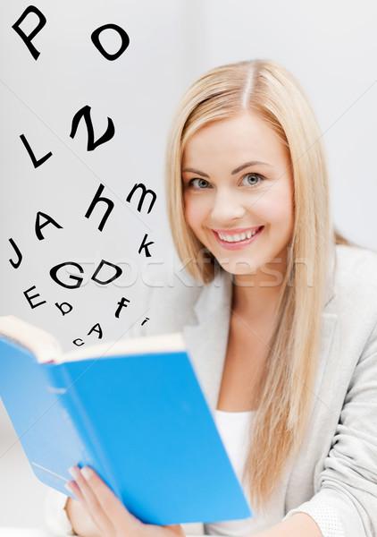 Genç kadın okuma kitap resim gülen ofis Stok fotoğraf © dolgachov