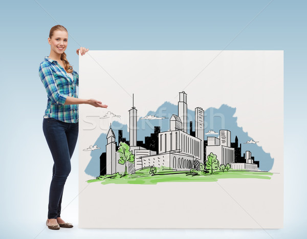 smiling young woman with board and city drawing Stock photo © dolgachov