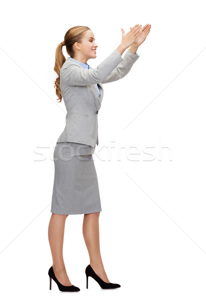 smiling businesswoman holding something imaginary Stock photo © dolgachov
