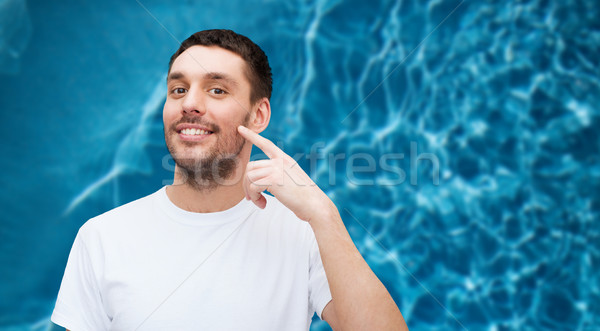 Glimlachend jonge knappe man wijzend wang gezondheid Stockfoto © dolgachov