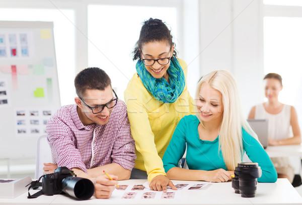 Glimlachend team afgedrukt foto's werken kantoor Stockfoto © dolgachov