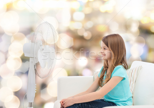 Stock photo: smiling little girl with big fan at home