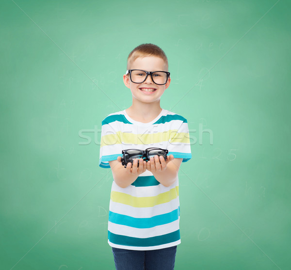 smiling boy in eyeglasses holding spectacles Stock photo © dolgachov