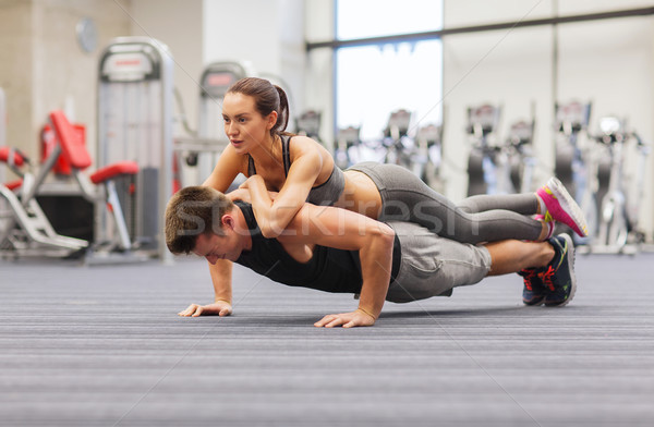smiling couple doing push-ups in the gym Stock photo © dolgachov