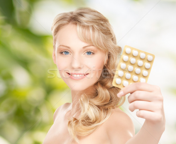 happy young woman holding package of pills Stock photo © dolgachov