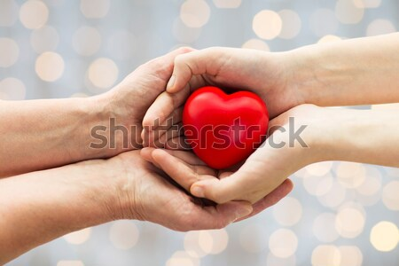 close up of male gay couple hands with red heart Stock photo © dolgachov
