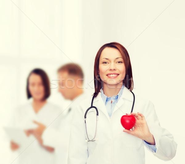 smiling female doctor with heart and stethoscope Stock photo © dolgachov