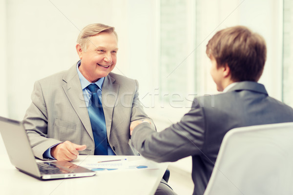 older man and young man shaking hands in office Stock photo © dolgachov