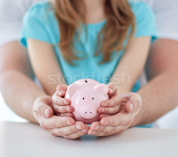 close up of family hands with piggy bank Stock photo © dolgachov