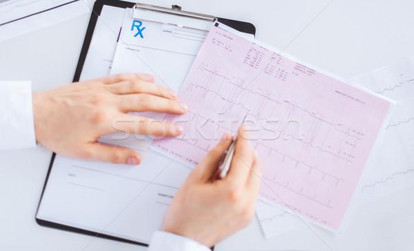 Médecin de sexe masculin mains cardiogramme lumineuses photos famille Photo stock © dolgachov