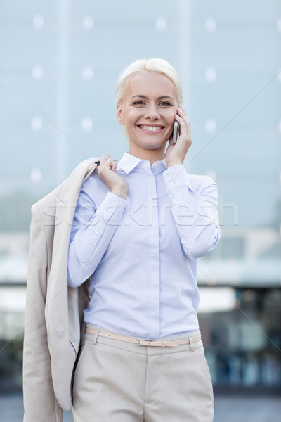Stock photo: smiling businesswoman with smartphone outdoors