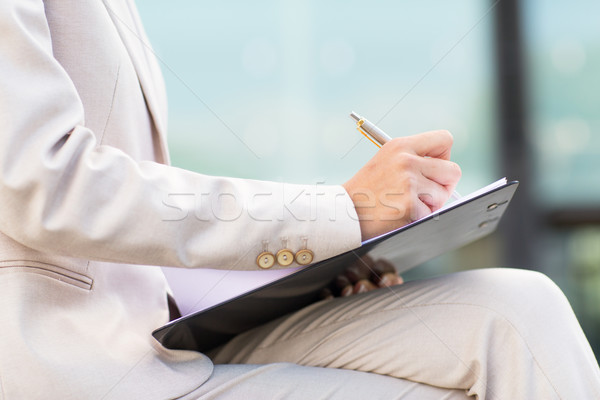 close up of business woman writing to clipboard Stock photo © dolgachov