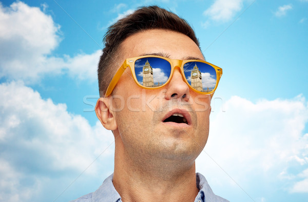 face of man in sunglasses looking at big ben tower Stock photo © dolgachov