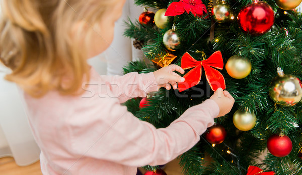 Stock photo: close up of little girl decorating christmas tree