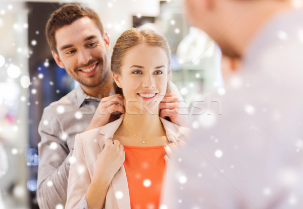 couple trying golden pendant on at jewelry store Stock photo © dolgachov