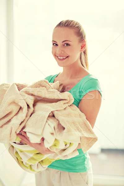 happy woman carrying clothes to laundry at home Stock photo © dolgachov