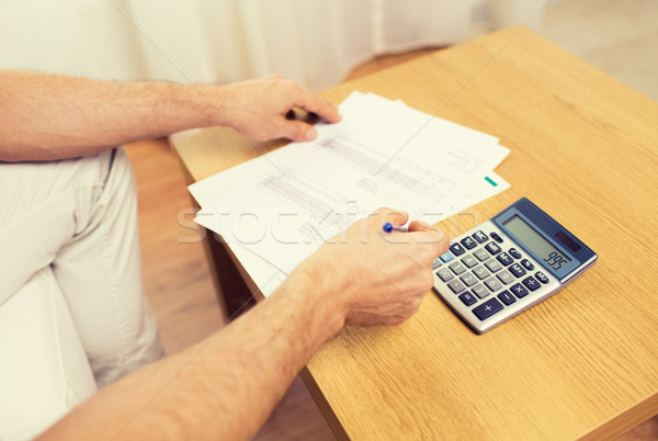 close up of man with papers and calculator at home Stock photo © dolgachov