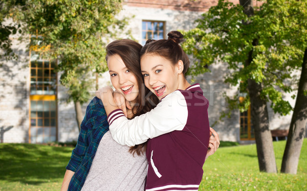 happy teenage student girls hugging over campus  Stock photo © dolgachov
