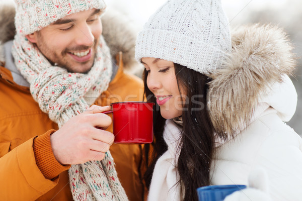 happy couple with tea cups over winter landscape Stock photo © dolgachov