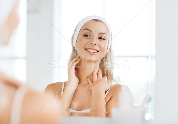 woman in hairband touching her face at bathroom Stock photo © dolgachov