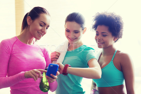 happy women showing time on wrist watch in gym Stock photo © dolgachov