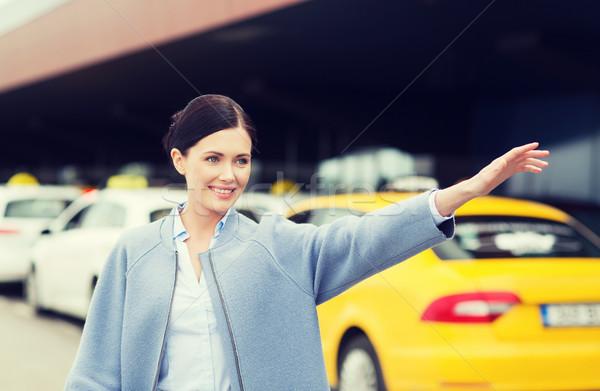 Mosolyog fiatal nő integet kéz taxi utazás Stock fotó © dolgachov