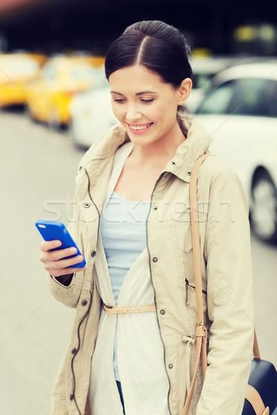 улыбающаяся женщина смартфон такси город путешествия командировка Сток-фото © dolgachov