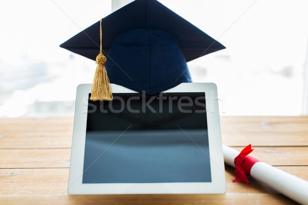 close up of tablet pc with mortarboard and diploma Stock photo © dolgachov