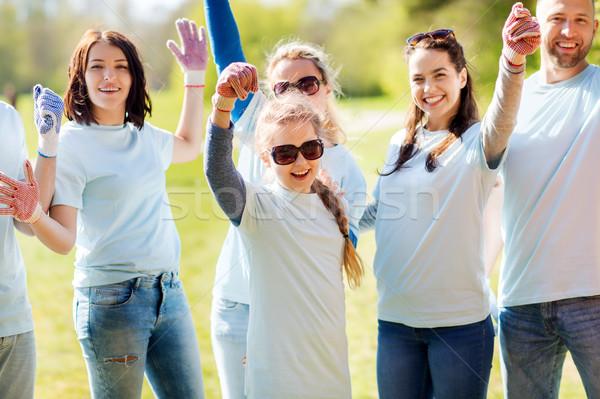 group of volunteers celebrating success in park Stock photo © dolgachov