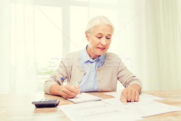 シニア 女性 論文 電卓 ホーム ビジネス ストックフォト © dolgachov