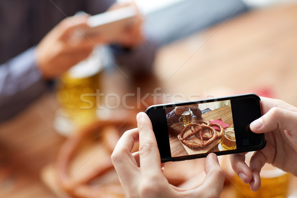 close up of hands picturing pretzel by smartphone Stock photo © dolgachov