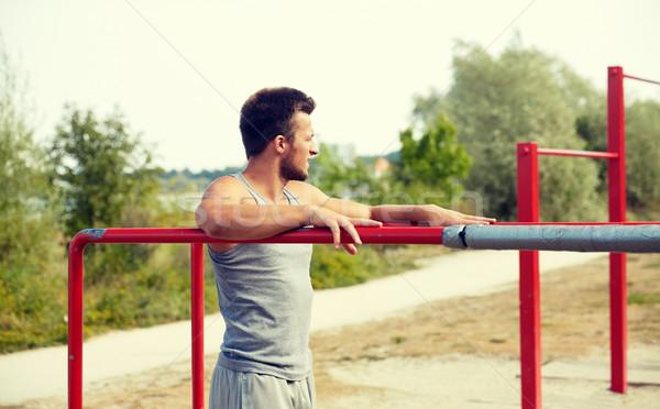 Jonge man parallel bars buitenshuis fitness Stockfoto © dolgachov