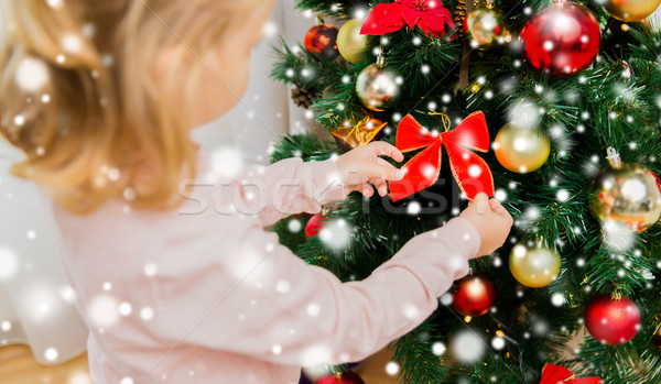close up of little girl decorating christmas tree Stock photo © dolgachov