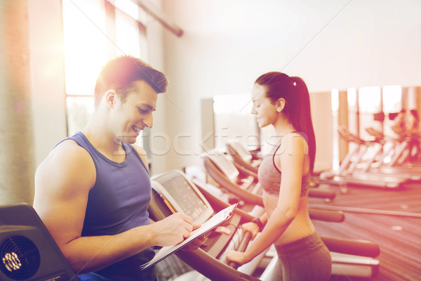 happy woman with trainer on treadmill in gym Stock photo © dolgachov