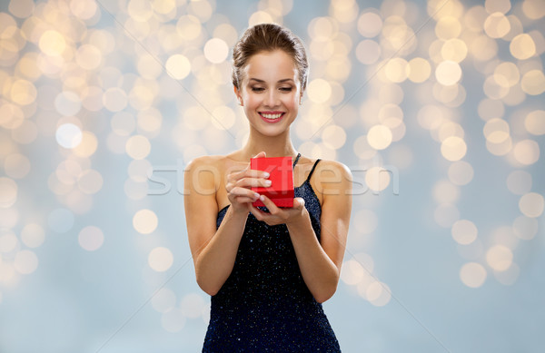 smiling woman holding red gift box over lights Stock photo © dolgachov