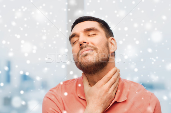 unhappy man suffering from throat pain over snow Stock photo © dolgachov