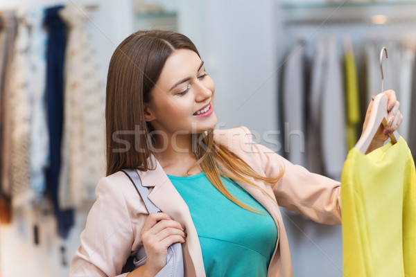 Stock photo: happy young woman choosing clothes in mall