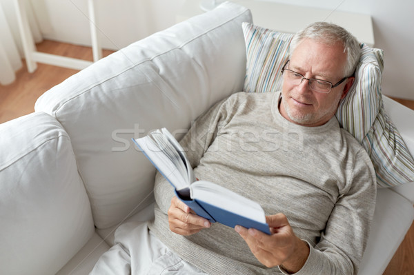 senior man lying on sofa and reading book at home Stock photo © dolgachov
