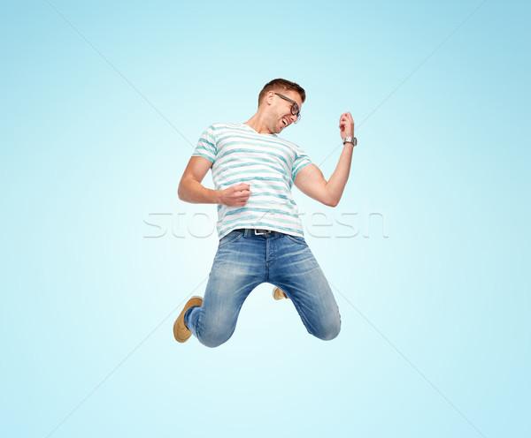 happy man jumping and playing imaginary guitar Stock photo © dolgachov