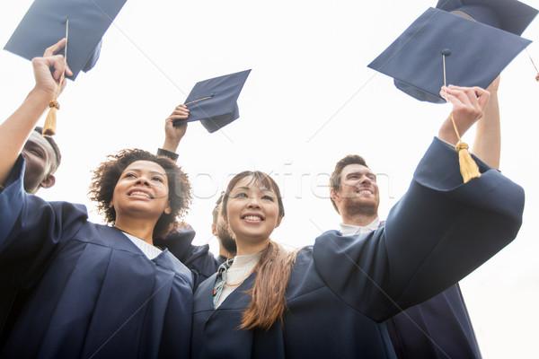 happy students or bachelors waving mortar boards Stock photo © dolgachov