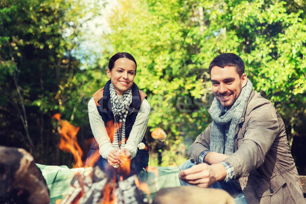 happy couple roasting marshmallow over camp fire Stock photo © dolgachov
