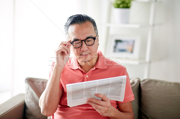 happy man in glasses reading newspaper at home Stock photo © dolgachov
