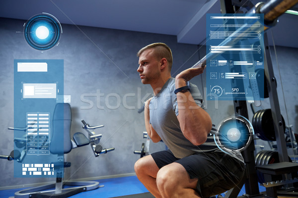 young man flexing muscles with barbell in gym Stock photo © dolgachov