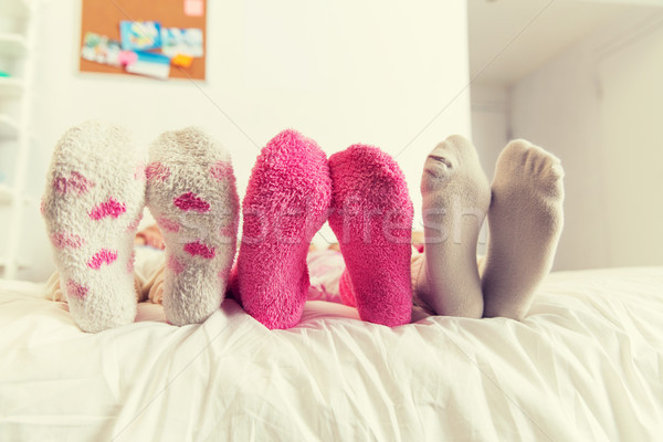 close up of women feet in socks on bed at home Stock photo © dolgachov