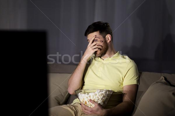 Ijedt férfi néz tv eszik pattogatott kukorica Stock fotó © dolgachov