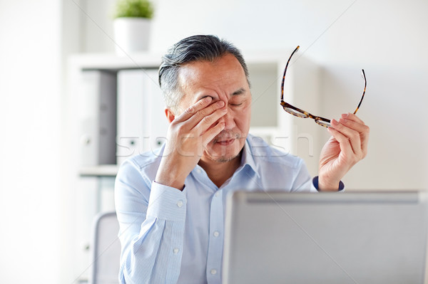 tired businessman with glasses at laptop in office Stock photo © dolgachov