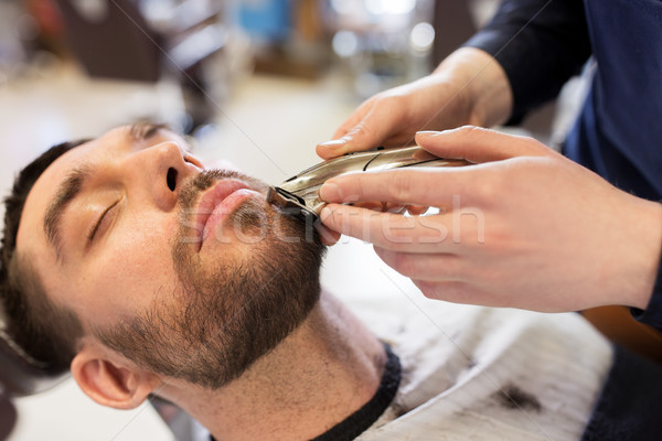 man and barber with trimmer cutting beard at salon Stock photo © dolgachov