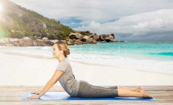 woman doing yoga in dog pose on beach Stock photo © dolgachov