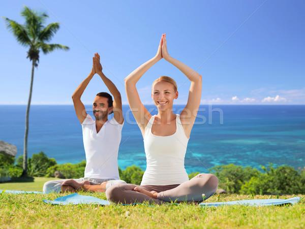 couple doing yoga in lotus pose outdoors Stock photo © dolgachov